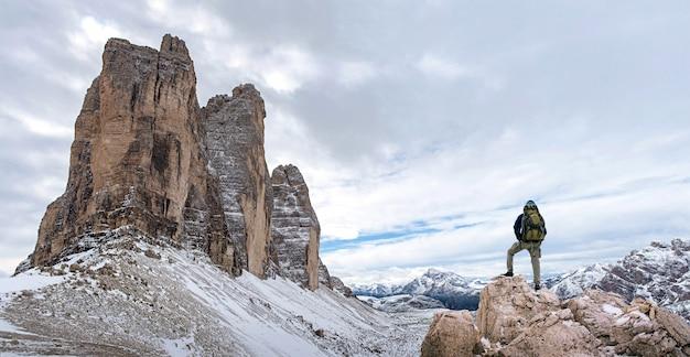 Silhouette des mannes auf dem gipfel des berges auf sonnenaufgangshimmel, sport und aktives leben konzeptionell.