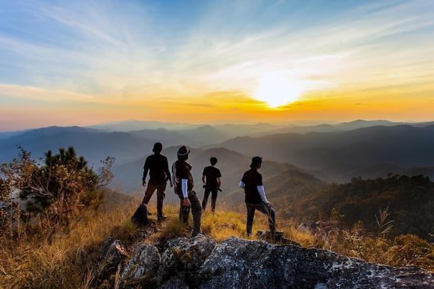 Silhouette des mannes halten hände auf dem gipfel des berges, erfolgskonzept