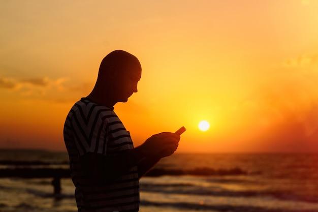 Silhouette des mannes mit telefon mit sonnenuntergang