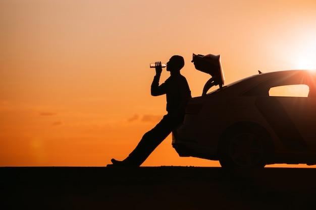 Silhouette des mannfahrers, der sich nach einer fahrt entspannt, auf dem kofferraum seines autos sitzt und wasser aus einer flasche trinkt