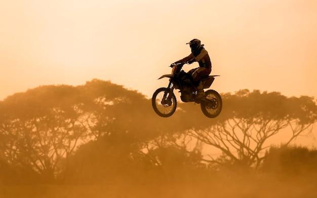 Silhouette des motocross-fahrers, der in spur springt