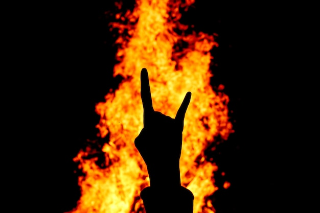Silhouette des rock'n'roll-handzeichens gegen das feuer