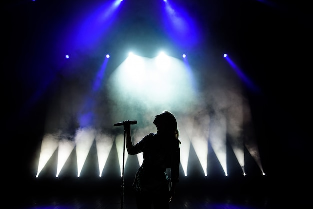 Silhouette des sängers auf der bühne. dunkler hintergrund, rauch, scheinwerfer.