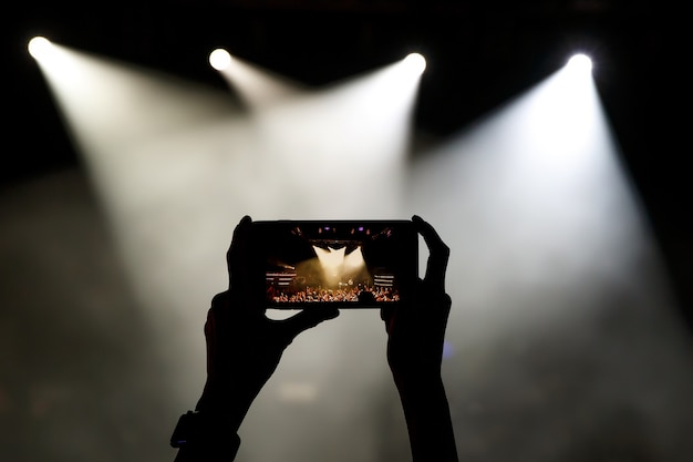 Silhouette des smartphones in den händen der frauen auf der konzertshow