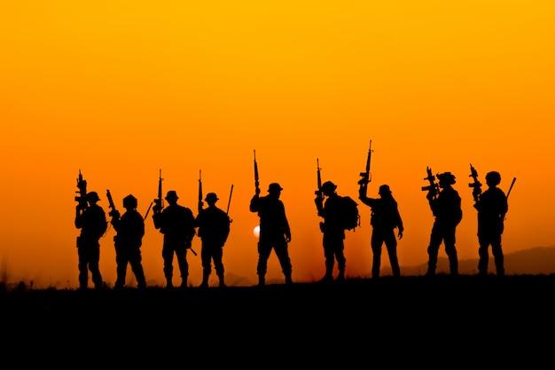 Silhouette des soldatenteams im sonnenuntergangshimmel. soldat mit maschinengewehr patrouilliert