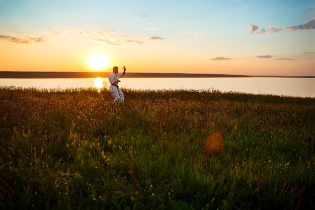 Silhouette des sportlichen mannes, der karate im feld bei sonnenaufgang trainiert.