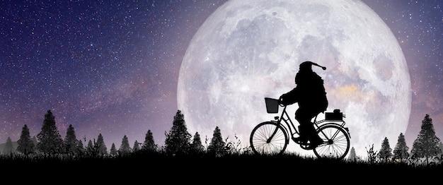 Silhouette des weihnachtsmannes, der auf seinem fahrrad fährt, um ein geschenk mit vollmondnacht zu tragen
