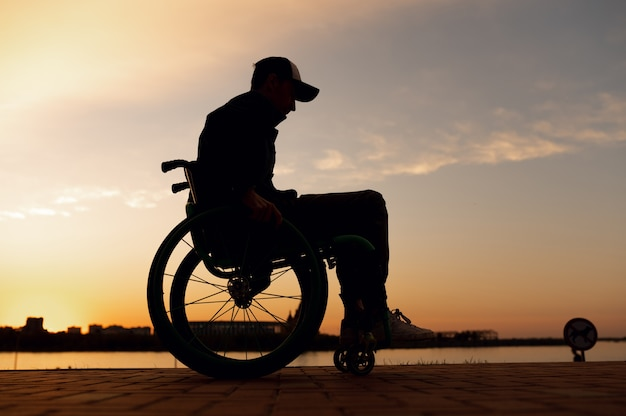 Silhouette einer behinderten person im rollstuhl auf dem hintergrund des sonnenuntergangs hochwertiges foto