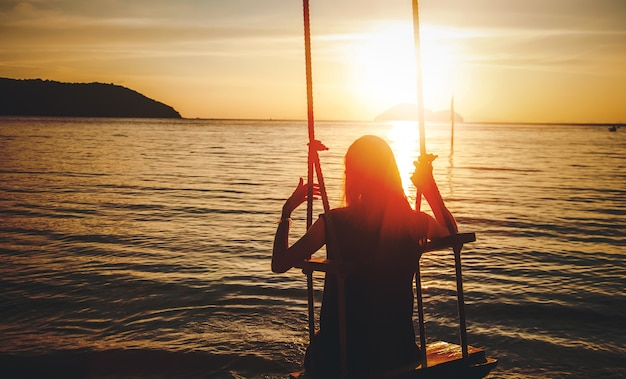 Silhouette einer frau auf einer schaukel bei sonnenuntergang am meer, meditation naturbeobachtungsurlaub und solo-reisekonzept