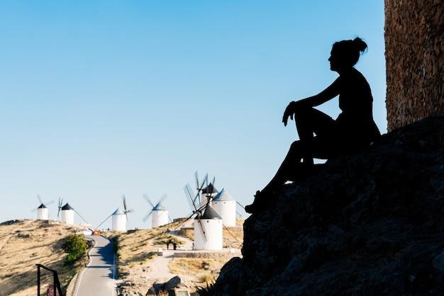 Silhouette einer frau, die auf den wänden einer mittelalterlichen burg sitzt und antike windmühlen in toledo, spanien, betrachtet.