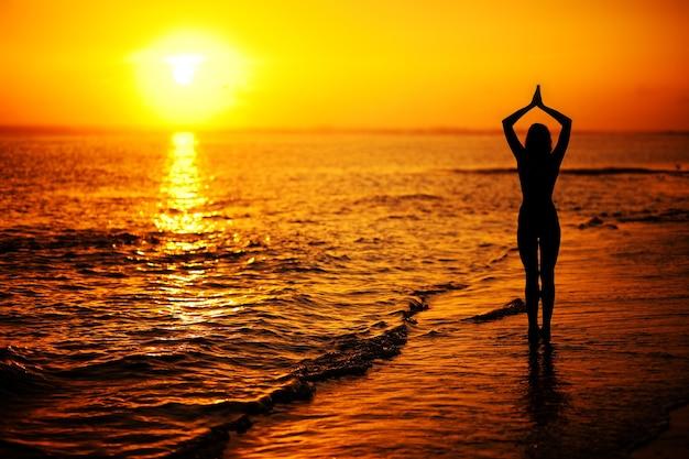 Silhouette einer frau, die bei sonnenuntergang am strand yoga-asanas macht