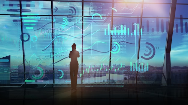 Silhouette einer geschäftsfrau und einer großen reihe von infografiken vor dem panoramafenster eines dunklen büros