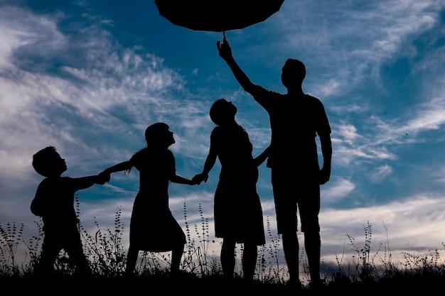 Silhouette einer glücklichen familie mit kindern mit regenschirm