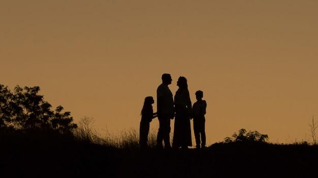Silhouette einer glücklichen vierköpfigen familie, mutter, vater, tochter, sohn bei sonnenuntergang