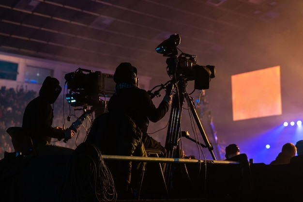 Silhouette einer gruppe von kameraleuten, die ein ereignis ausstrahlen. die arbeiter sind auf einer hohen plattform