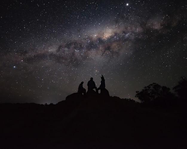 Silhouette einer gruppe von personen, die auf einem felsen sitzen und die milchstraße beobachten