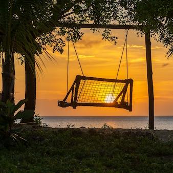 Silhouette einer holzschaukel mit wunderschönem sonnenuntergang am tropischen strand in der nähe von meer, insel sansibar, tansania, ostafrika
