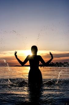 Silhouette einer jungen frau mit spritzwasser in form eines herzens auf einem des meeres