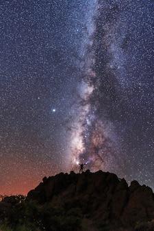 Silhouette einer jungen frau unter den sternen, die die milchstraße in der nacht betrachten, astrofotografie