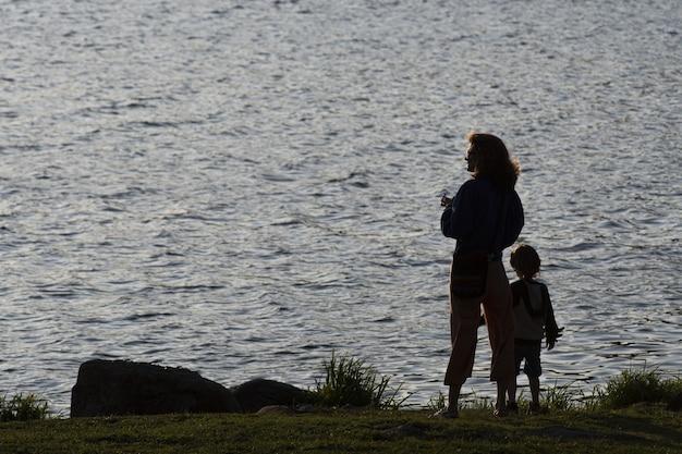 Silhouette einer mutter und ihres sohnes gegen eine lagune bei sonnenuntergang