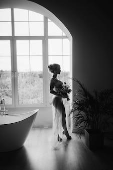 Silhouette einer weiblichen braut mit einem blumenstrauß auf dem hintergrund des badezimmerfensters