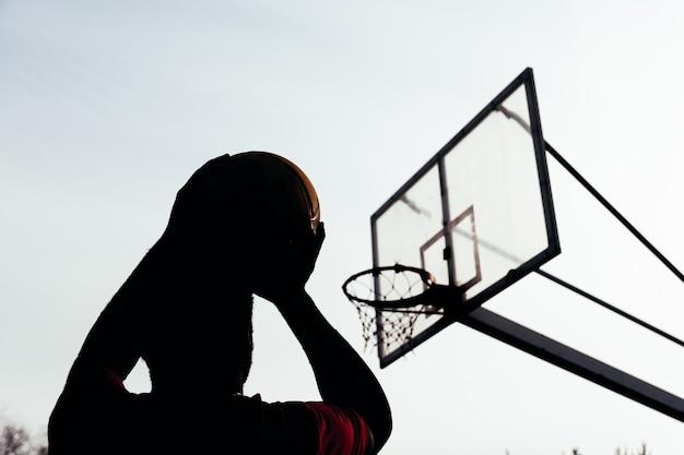 Silhouette eines afroamerikanischen schwarzen jungen, der bereit ist, den ball in den korb zu schießen. rückansicht.