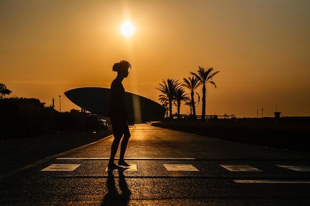 Silhouette eines afroamerikanischen surfers, der bei sonnenaufgang mit surfbrett geht