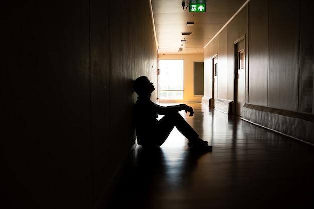 Silhouette eines depressiven mannes, der auf dem gehweg des wohngebäudes sitzt, das ein trauriges einsames unglückliches konzept baut