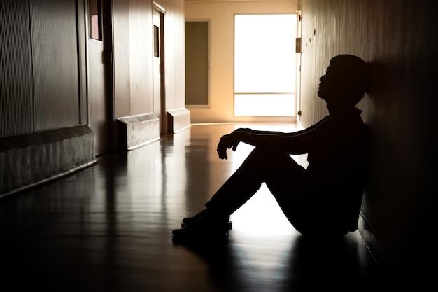 Silhouette eines depressiven mannes, der auf dem gehweg des wohngebäudes sitzt trauriges einsames unglückliches konzept