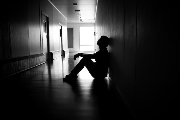 Silhouette eines depressiven mannes, der auf dem gehweg des wohngebäudes sitzt trauriges und einsames konzept