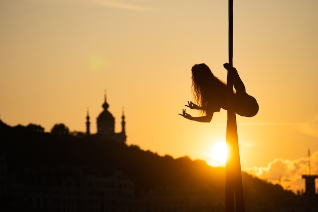 Silhouette eines flexiblen frauenakrobaten auf luftseide während eines sonnenuntergangs auf kiewer stadthintergrund. konzept von freiheit und frieden.