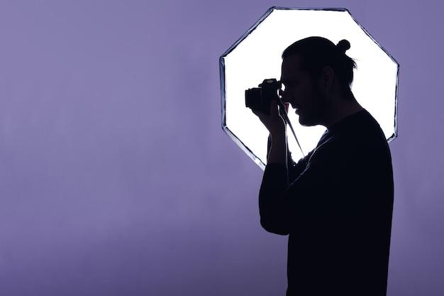 Silhouette eines fotografen, der die kamera vor einem blitz hält