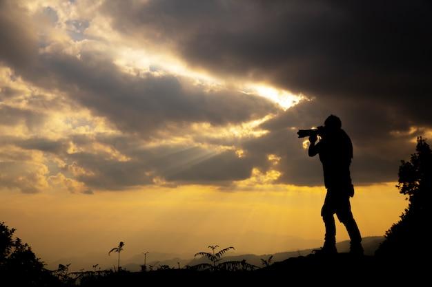 Silhouette eines fotografen, der einen sonnenuntergang in den bergen schießt