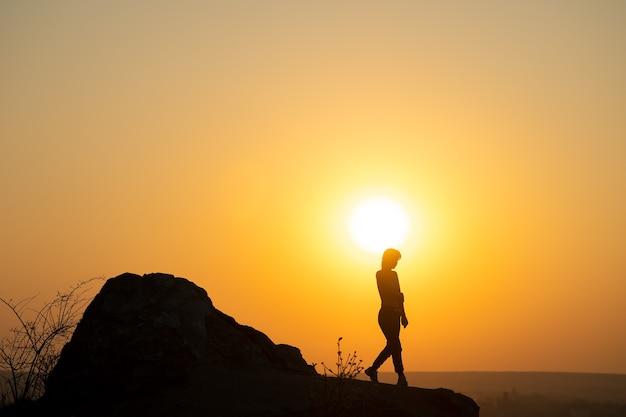 Silhouette eines frauenwanderers, der bei sonnenuntergang in den bergen einen großen stein hinuntergeht.
