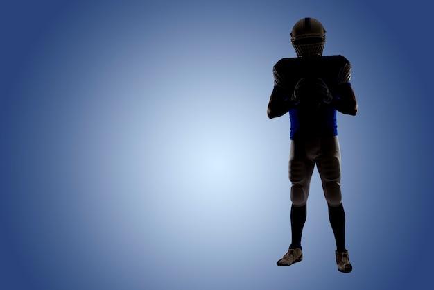 Silhouette eines fußballspielers mit einer blauen uniform auf einer blauen wand