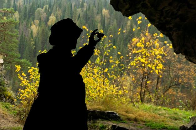 Silhouette eines geologen, der eine in einer höhle gefundene mineralprobe untersucht
