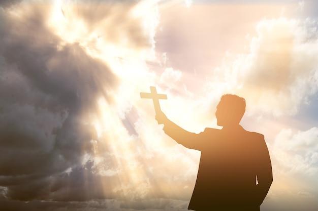 Silhouette eines geschäftsmannes, der christliches kreuz mit einem dramatischen himmel hält