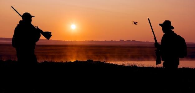 Silhouette eines jägers auf dem hintergrund der roten morgendämmerung. steht mit einer waffe bereit.