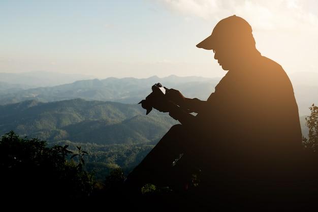Silhouette eines jungen, der gerne reist und fotografiert, fotografiert die wunderschönen momente während des sonnenuntergangs, sonnenaufgangs und berges