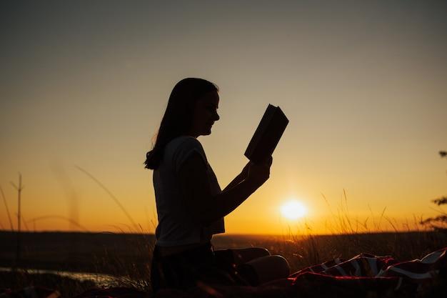Silhouette eines jungen hübschen schönen mädchens bei erstaunlichem sonnenuntergang, der auf einer spitze des hügels mit fluss auf hintergrund sitzt und sorgfältig auf das offene buch starrt.
