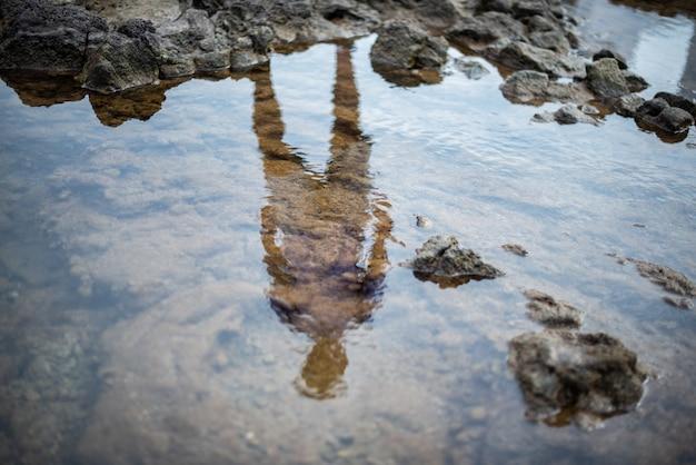 Silhouette eines jungen mannes, der sich im wasser spiegelt