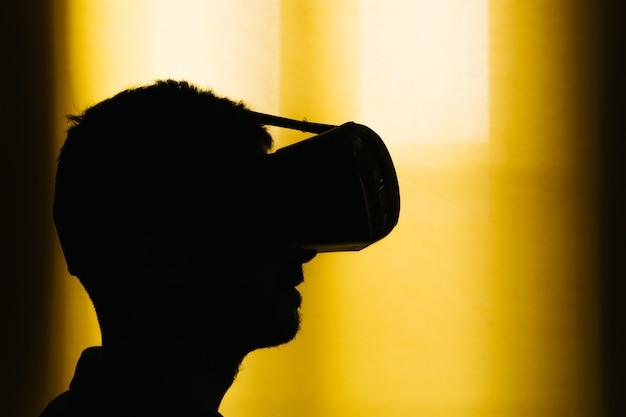 Silhouette eines jungen mannes mit einem virtual-reality-headset, vr. gelber hintergrund mit textfreiraum