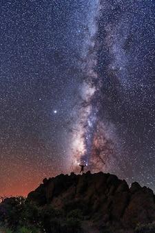 Silhouette eines jungen mannes unter den sternen, der die milchstraße in der nacht betrachtet, astrofotografie