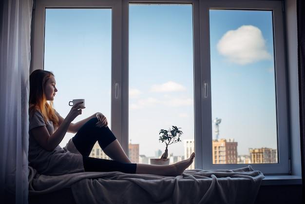 Silhouette eines jungen schlanken mädchens, das zu hause auf der fensterbank sitzt, seitenansicht, kopierraum. vor dem fenster blauer himmel und hohe stadtgebäude. rothaarige frau mit tasse, blick auf die metropole.