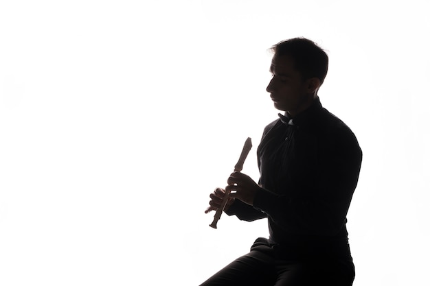 Silhouette eines künstlers, der die flöte spielt