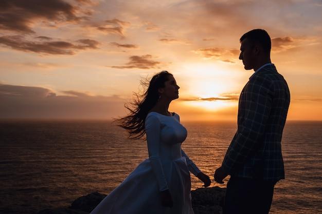 Silhouette eines liebevollen paares bei sonnenuntergang, mit meereshintergrund