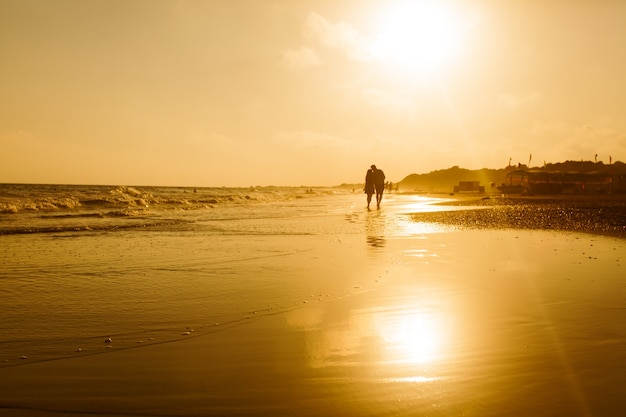 Silhouette eines liebevollen paares, das einen sandstrand entlang geht und den sonnenuntergang genießt