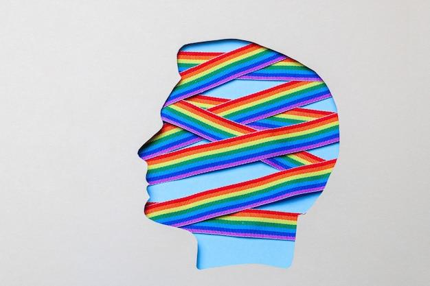 Silhouette eines männlichen kopfes und regenbogenbänder des lgbt-stolzes. schwul im kopf drinnen.