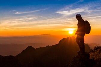 Silhouette eines Mannes auf einem Berggipfel. Personenschattenbild auf dem Felsen.