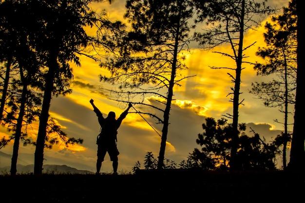 Silhouette eines mannes, der klettert und am terminalweg glücklich ist
